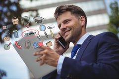 Hombre de negocios feliz usando el teléfono elegante y la tableta digital con los diversos iconos de la búsqueda de trabajo Fotografía de archivo libre de regalías