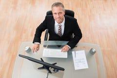 Hombre de negocios feliz Using Computer Foto de archivo libre de regalías