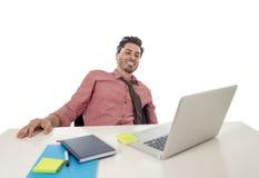 Hombre de negocios feliz y atractivo joven en camisa y lazo que se sienta en el escritorio de oficina que trabaja con el ordenado Imágenes de archivo libres de regalías