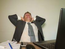Hombre de negocios feliz y atractivo joven que trabaja en el comput de la oficina imagenes de archivo