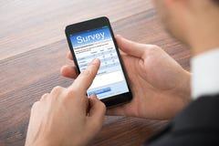 Hombre de negocios Filling Online Survey en el teléfono móvil Foto de archivo