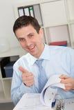 Hombre de negocios Flipping Through Book que da los pulgares para arriba foto de archivo libre de regalías