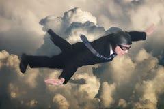 Hombre de negocios Fly en nubes, viaje sobre la tierra Foto de archivo libre de regalías