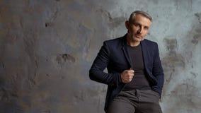 Hombre de negocios fresco con el pelo gris y barba en fondo gris imagen de archivo libre de regalías