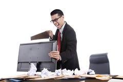 Hombre de negocios frustrado que asierra su computadora Imágenes de archivo libres de regalías