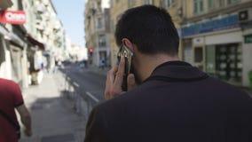 Hombre de negocios frustrado que discute problemas en el teléfono y la calle de la ciudad que camina metrajes
