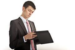Hombre de negocios frustrado que muerde su tablilla del ordenador Fotos de archivo libres de regalías