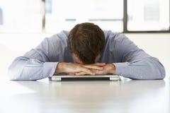 Hombre de negocios frustrado Sitting At Desk en oficina usando el ordenador portátil Foto de archivo libre de regalías