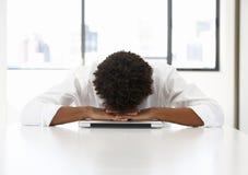 Hombre de negocios frustrado Sitting At Desk en oficina usando el ordenador portátil Fotografía de archivo libre de regalías