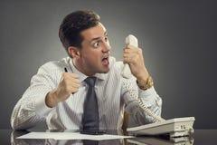 Hombre de negocios furioso que grita en el teléfono Imágenes de archivo libres de regalías