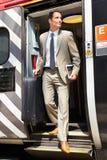 Hombre de negocios Getting Off Train en la plataforma Fotos de archivo libres de regalías