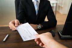 Hombre de negocios Giving Cheque To la otra persona Fotos de archivo