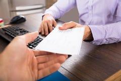 Hombre de negocios Giving Cheque To su colega imagen de archivo libre de regalías