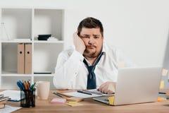hombre de negocios gordo aburrido que trabaja con la libreta y el ordenador portátil fotografía de archivo libre de regalías