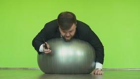 Hombre de negocios gordo en mentiras negras del traje en la bola del ejercicio, hablando en smartphone en gimnasio El jefe regord almacen de video