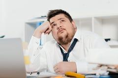 hombre de negocios gordo pensativo con el ordenador portátil en el lugar de trabajo imagenes de archivo