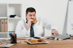 hombre de negocios gordo que come la hamburguesa y que usa el ordenador portátil imagen de archivo libre de regalías