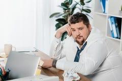 hombre de negocios gordo que se sienta en el lugar de trabajo con los papeles arrugados foto de archivo libre de regalías