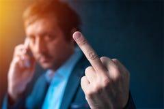 Hombre de negocios grosero que habla en el teléfono y que da el dedo medio Imagen de archivo