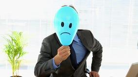 Hombre de negocios gruñón que sostiene el globo triste de la cara sobre cara metrajes
