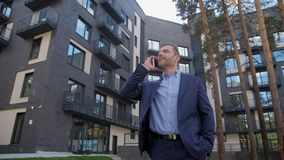 Hombre de negocios hablar en el smartphone al aire libre cerca de hogar almacen de video