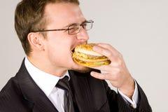 Hombre de negocios hambriento que come la hamburguesa imagen de archivo libre de regalías