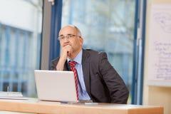 Hombre de negocios With Hand On Chin Looking Away At Desk Fotografía de archivo