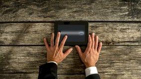 Hombre de negocios Hand Holding Tablet en la tabla Imagenes de archivo