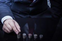 Hombre de negocios Hand Put Coins a la pila de monedas Imagen de archivo libre de regalías