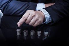 Hombre de negocios Hand Put Coins a la pila de monedas Fotos de archivo