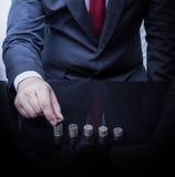 Hombre de negocios Hand Put Coins a la pila de monedas Imagen de archivo