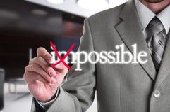 Hombre de negocios Hand que da vuelta a la palabra imposible en Imágenes de archivo libres de regalías