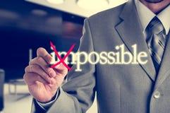 Hombre de negocios Hand que da vuelta a la palabra imposible en posible con el marcador rojo Fotografía de archivo