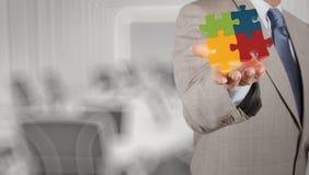 Hombre de negocios Hand que muestra el rompecabezas 3d Imagen de archivo