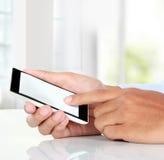 Hombre de negocios Hand que sostiene el teléfono elegante móvil con la pantalla en blanco Imagen de archivo libre de regalías