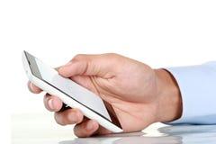 Hombre de negocios Hand que sostiene el teléfono elegante móvil con la pantalla en blanco Imágenes de archivo libres de regalías
