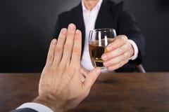 Hombre de negocios Hand Rejecting al vidrio de whisky Imagen de archivo libre de regalías