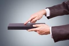 Hombre de negocios Hand Touching Book como tableta Fotos de archivo