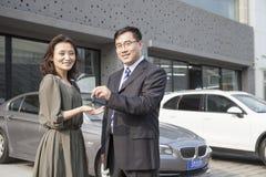 Hombre de negocios Handing Car Keys a la mujer en taller de reparaciones auto Fotografía de archivo libre de regalías