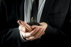 Hombre de negocios Hands Holding Soil con el brote joven Imagen de archivo