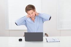 Hombre de negocios Having Neck Pain mientras que trabaja en el ordenador portátil Imagenes de archivo