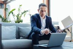 Hombre de negocios hermoso acertado que señala en la pantalla del ordenador portátil foto de archivo libre de regalías