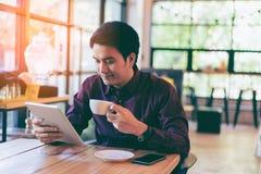 Hombre de negocios hermoso asiático joven que sonríe mientras que lee su tabla Foto de archivo