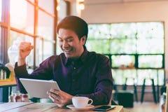 Hombre de negocios hermoso asiático joven que sonríe mientras que lee su tabla Fotografía de archivo