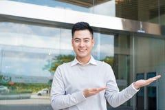 Hombre de negocios hermoso con el brazo hacia fuera en un gesto que da la bienvenida Foto de archivo