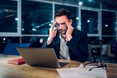 Hombre de negocios hermoso con el trabajo del ordenador portátil latenight foto de archivo