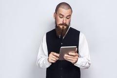 Hombre de negocios hermoso con la tenencia del bigote de la barba y del manillar y usar la tableta digital Fotos de archivo libres de regalías