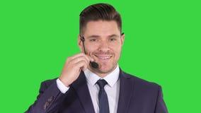 Hombre de negocios hermoso con las auriculares que miran en c?mara y que sonr?en en una pantalla verde, llave de la croma metrajes