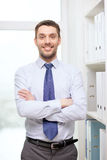 Hombre de negocios hermoso con los brazos cruzados en la oficina Fotos de archivo libres de regalías