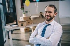 hombre de negocios hermoso con los brazos cruzados que sonríe en la cámara en la nueva oficina adornada fotos de archivo